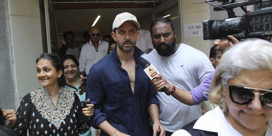 Bollywood star Hrithik Roshan, center, leaves after casting his vote at a polling station in Mumbai.
