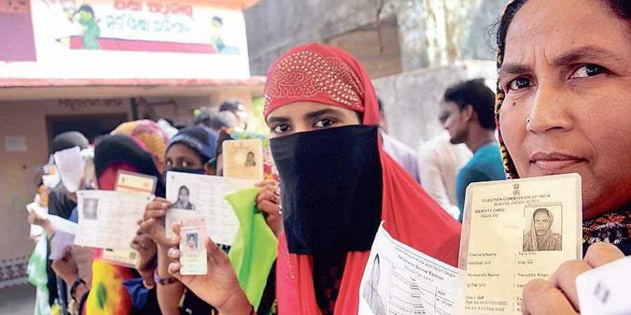 Muslim women voters showing their identity cards before casting votes at a polling station in Kendrapara district on Monday