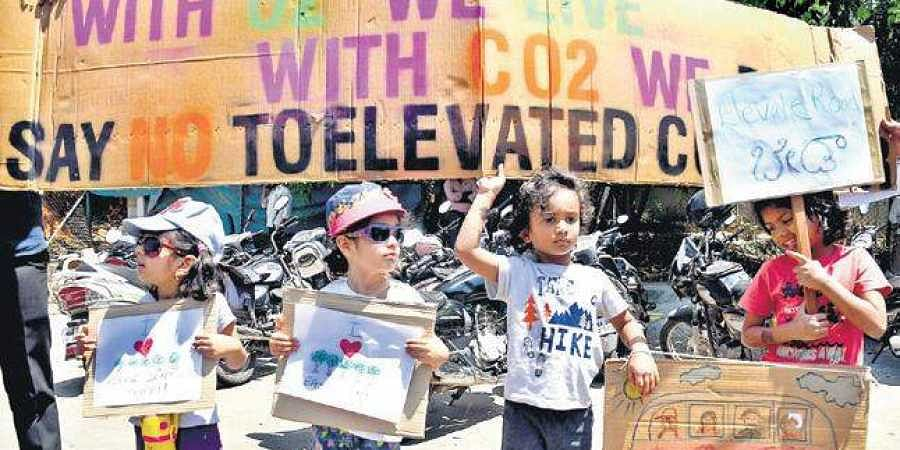 Children with placards join the protest against the proposed elevated corridor project at Maurya Circle in Bengaluru on Saturday