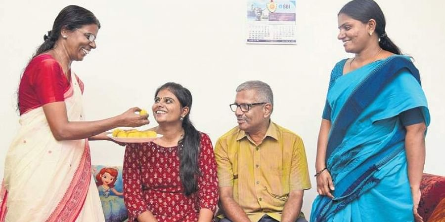 Sreelakshmi R greeted by her mother Kaladevi, father V A Ramachandran and sister Vidhya, at her residence in East Kadungalloor near Aluva on Saturday