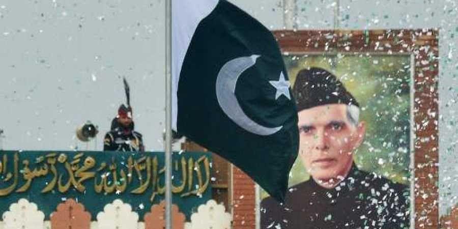The portrait of Muhammad Ali Jinnah is seen at at the India-Pakistan Wagah border post as a Pakistani Ranger (top) unfurls the Pakistani national flag