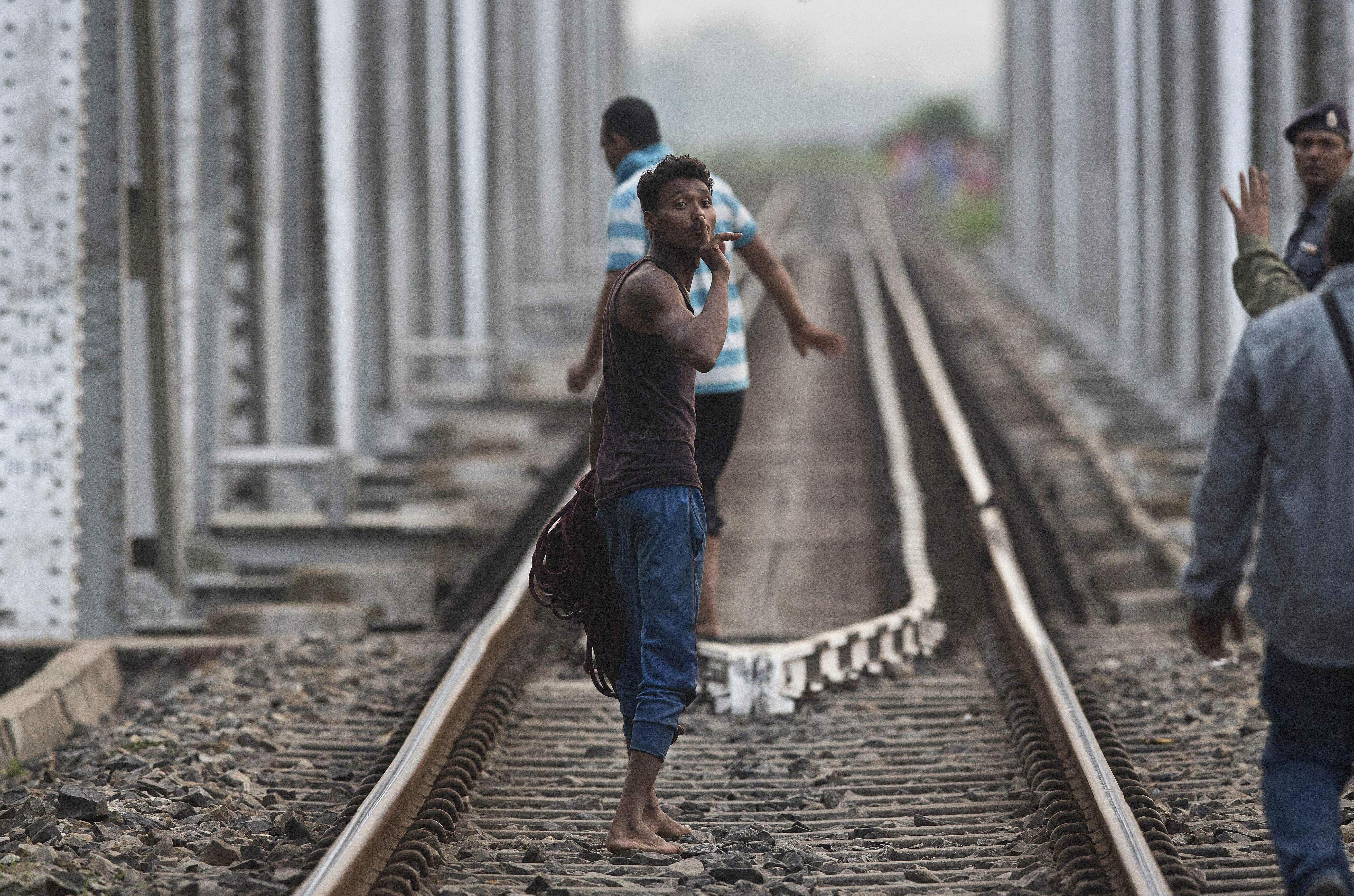 A villager gestures to the crowd to be quiet for fear of frightening a baby wild elephant crossing a road at Deepor Beel wildlife sanctuary in Gauhati.