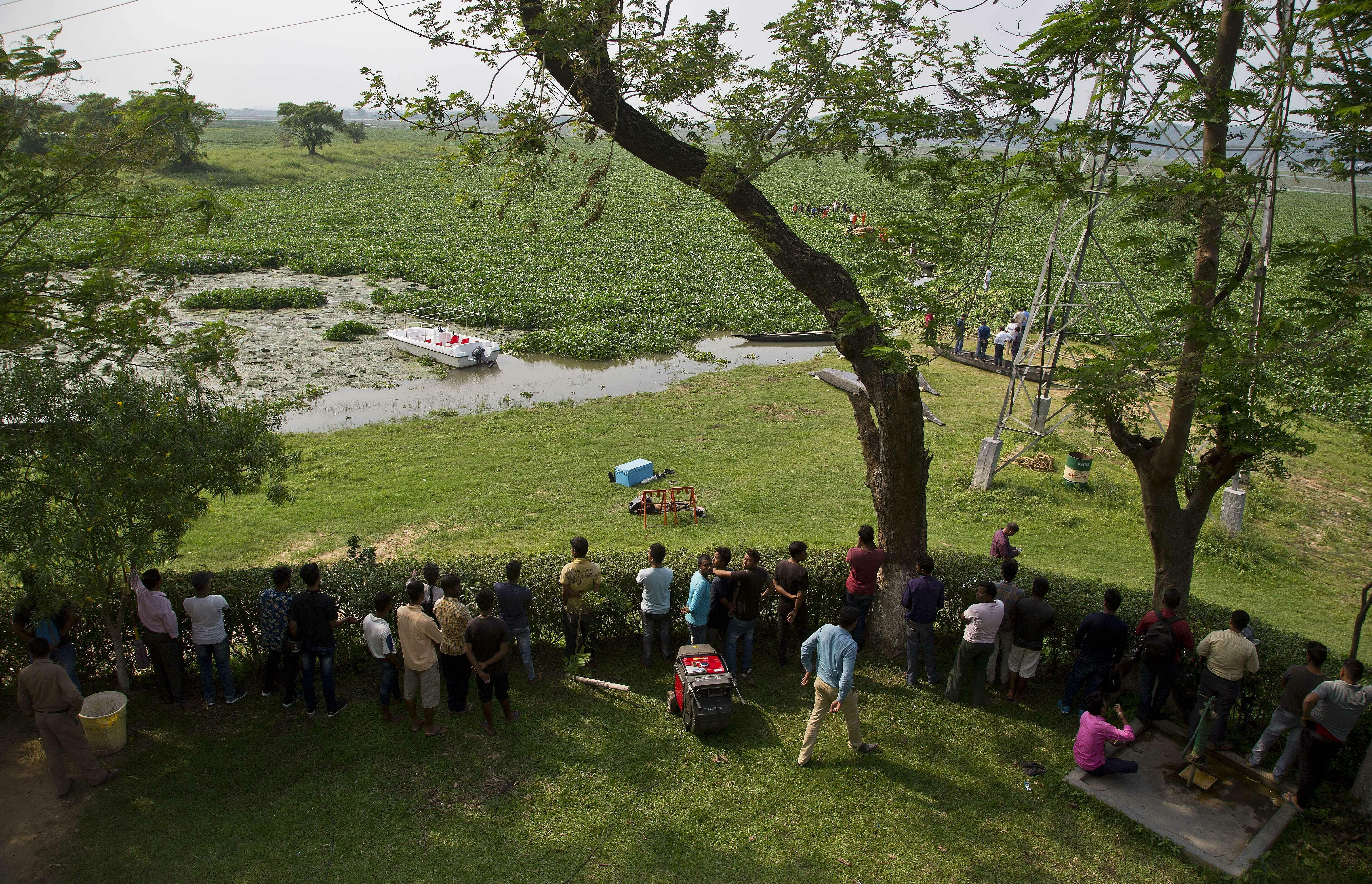 People watch rescuers help a baby wild elephant cross the wetland to return to the forest at Deepor Beel wildlife sanctuary in Gauhati.