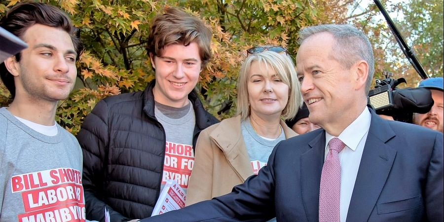 Australian Labor Party leader Bill Shorten, right, shakes hands with supporters at a polling station for a federal election in Melbourne.