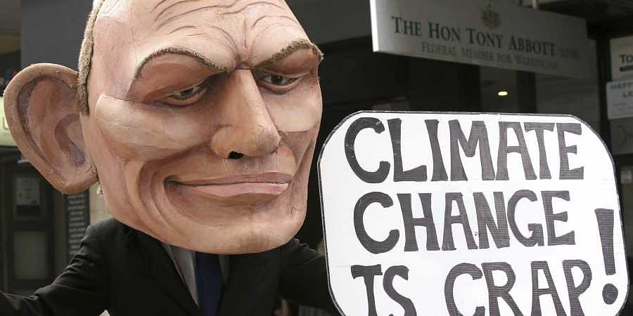 In this May 3, 2019, file photo, a demonstrator with a giant head in the likeness of former Australian Prime Minister Tony Abbott holds a sign referencing a comment by Abbott made in 2017 belittling the science of climate change, during a student organized protest at in Sydney.