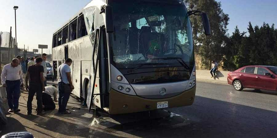 Officials inspect a bus that was damaged by a bomb in Cairo