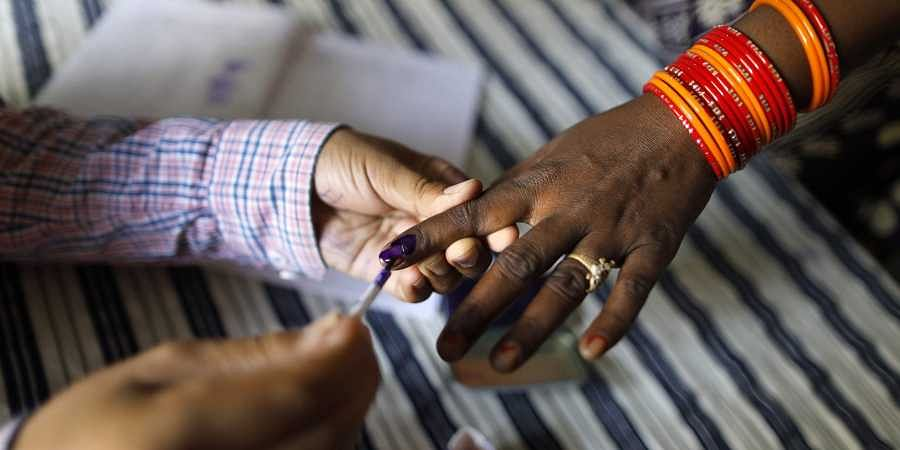 A polling officer puts indelible ink mark on the index finger of an women voter at a polling station.