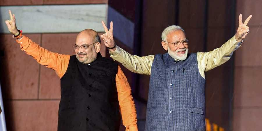 Prime Minister Narendra Modi flashes the victory sign along with party president Amit Shah as they arrive at the party headquarters to celebrate their victory in the 2019 Lok Sabha elections in New Delhi on 23 May 2019. (Photo   PTI)