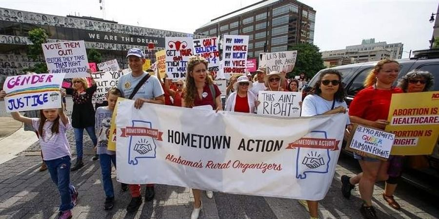 In this May 19, 2019, photo, protesters for women's rights march to the Alabama Capitol to protest a law passed last week making abortion a felony in nearly all cases with no exceptions for cases of rape or incest in Montgomery, Ala.
