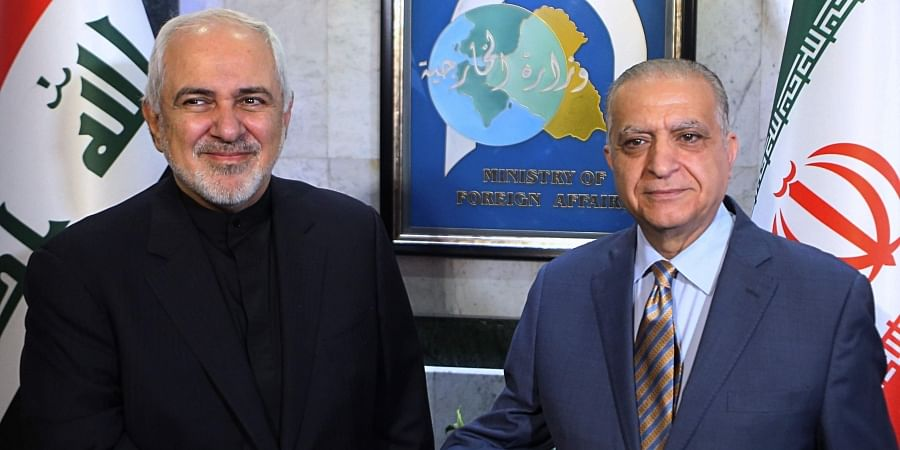 Iraqi Foreign Minister Mohamed Alhakim, right, shakes hands with his visiting Iranian counterpart Mohammad Javad Zarif at the Ministry of Foreign Affairs Building in Baghdad.