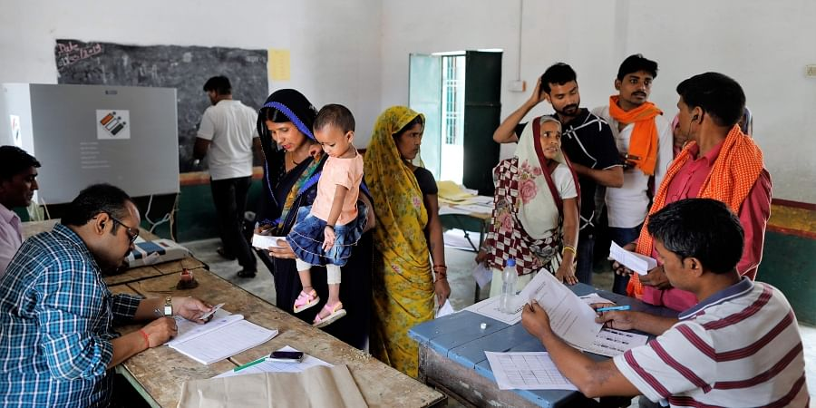 Election officers check the identity of voters before allowing them to cast their votes during the seventh and final phase of national elections, on the outskirts of Varanasi.