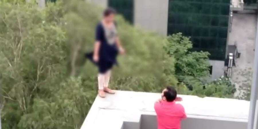 A woman inGurugram's Cyber City captured on cam standing atop a five-storey building threatening to jump.