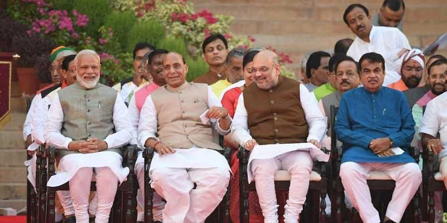 Narendra Modi (L) looks on as he sits next to Bharatiya Janata Party President Amit Shah (2R) and Minister of Home Affairs of India Rajnath Singh (2L) before Modi's swearing-in ceremony as Indian Prime Minister at the President house in New Delhi on Thursday