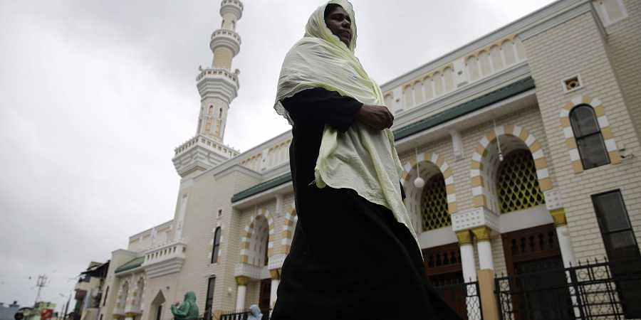 A Sri Lankan muslim woman walks past a mosque in Colombo, Sri Lanka.