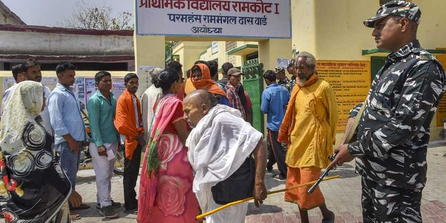 A security jawan stands guard as voters wait in a queue to cast their votes at a polling station during the fifth phase of the 2019 Lok Sabha elections in Ayodhya. (Photo | PTI)