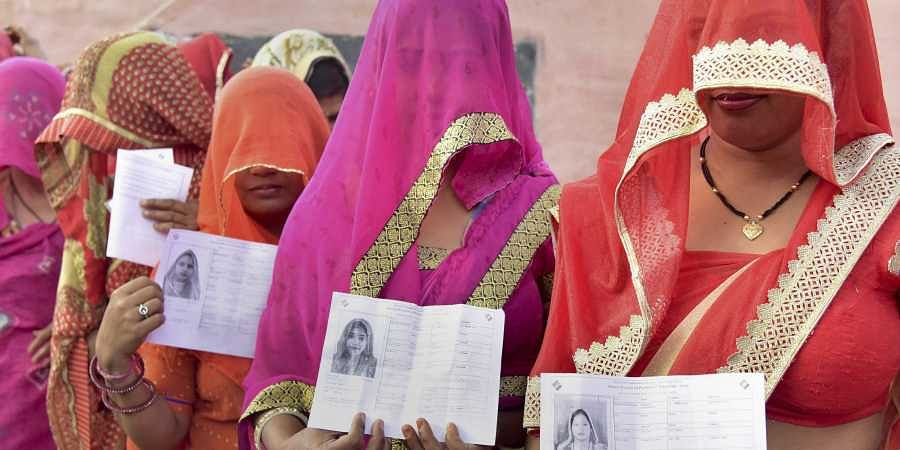 Voters show their voting cards as they wait in queue at a polling station during the fifth phase of Lok Sabha elections in Bikaner. (Photo | PTI)