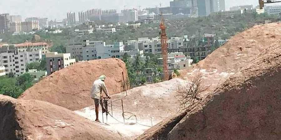 A construction worker seen drilling a hole into a boulder at Fakhruddin Gutta hillock on Saturday