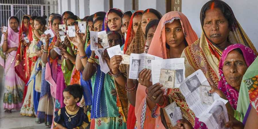 Women show their voter identity cards as they stand in a queue at a polling station during the 5th phase of Lok Sabha polls in Chhapra district of Bihar. (Photo | PTI)