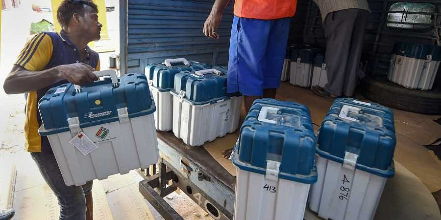 Workers carry boxes containing Electronic Voting Machines (EVM) and Voter Verified Paper Audit Trail machines (VVPATs) at a distribution centre.