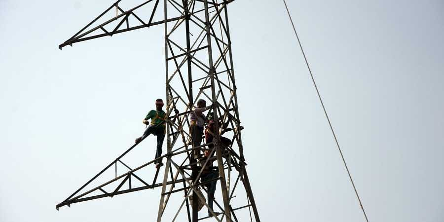 Workers busy repairing an electric tower on the outskirts of Bhubaneswar