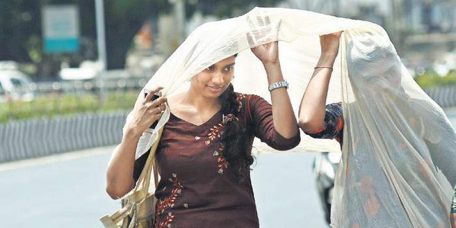 two women cover themselves with a dupatta to beat the heat | Ashwin Prasath