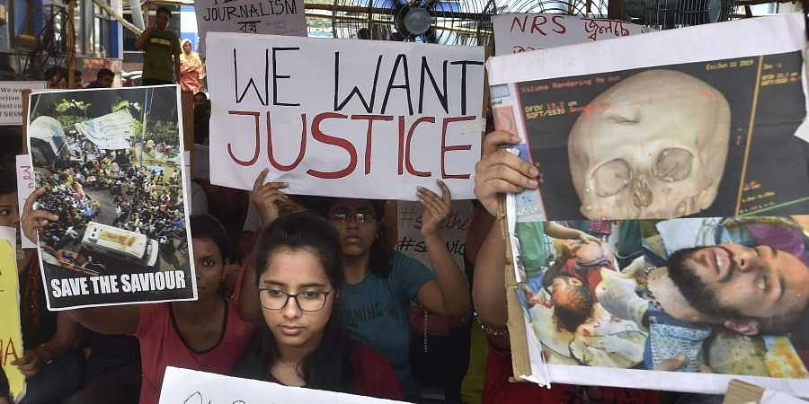 Junior doctors hold placards during a demonstration on 13 June 2019 after an intern doctor was attacked and seriously injured over the death of a 75-year-old patient at Nil Ratan Sircar Medical College and Hospital in Kolkata. (Photo | PTI)