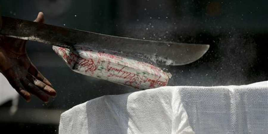Representational image of a narcotics agent using a machete to slice open a brick of cocaine