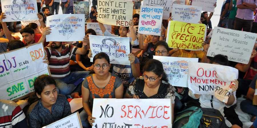 Junior doctors hold placards during their strike in protest against an attack on an intern doctor at Nil Ratan Sircar Medical College and Hospital in Kolkata on 14 June 2019. (Photo | PTI)