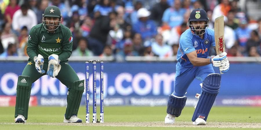 Pakistan's captain Sarfaraz Ahmed, left, reacts after India's captain Virat Kohli, right, played a shot during the Cricket World Cup match between India and Pakistan at Old Trafford in Manchester. (Photo | AP)