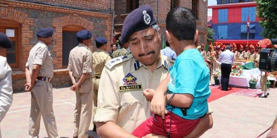 Haseeb Mughal, the Senior Superintendent of Police in Srinagar, breaks down while carrying the 4-year-old son, Uhbaan of inspector Arshad Khan who died in the Anantnag encounter on 17 June 2019. (Photo | Twitter)