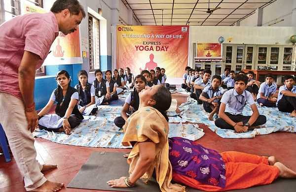 'Yoga for all', an initiative by The New Indian Express to spread awareness on yoga, was held at  St Joachim UP School, Kathrikadavu on Tuesday. S Ayyappan, yoga master, instructs students and a teacher during the yoga session | Albin Mathew