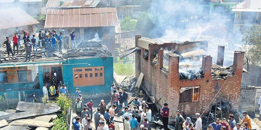 Locals gather outside the damaged houses where two top Jaish-e-Mohammed JeM militants were hiding during an encounter at Bijbehara area of Anantnag district on 18 June 2019. (Photo | Zahoor Punjabi, EPS)