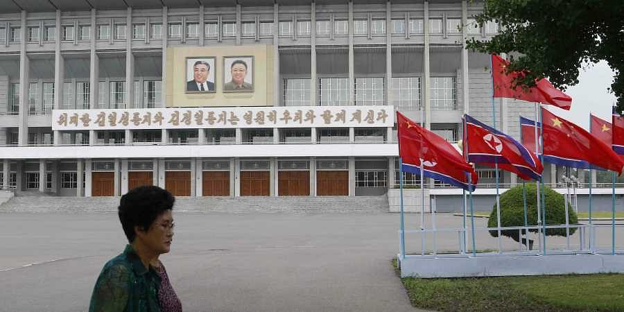 North Korean and Chinese national flags are hoisted on a street in Pyongyang, North Korea Thursday, June 20, 2019.
