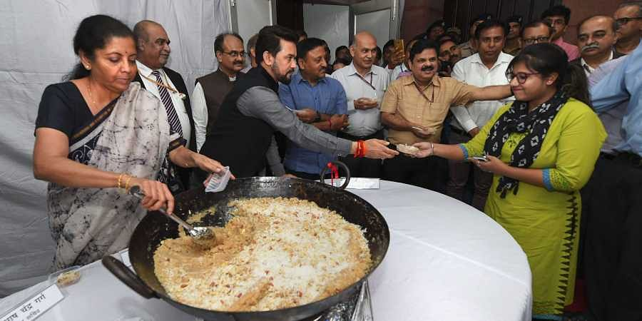 Union Minister for Finance Nirmala Sitharaman and MoS Anurag Thakur distribute halwa to officials during the 'Halwa Ceremony' to mark the beginning of printing of budgetary documents in New Delhi on 22 June 2019. (Photo | PTI)