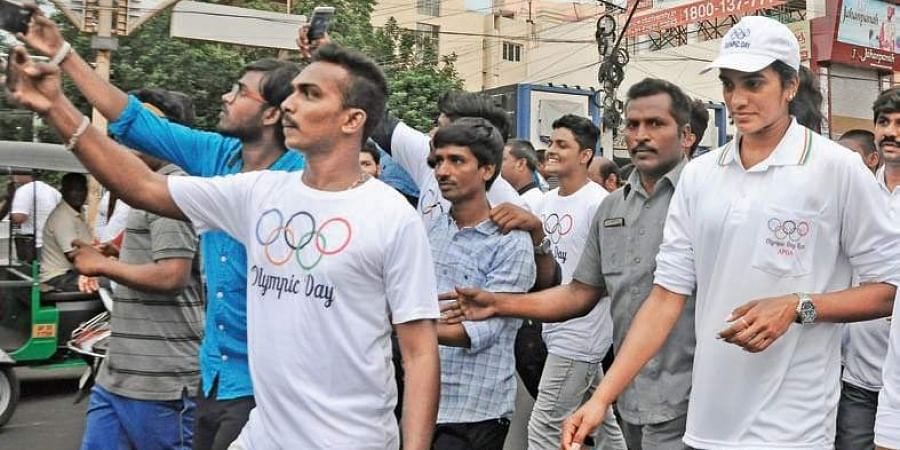 Athletes taking selfies with Olympics silver medallist PV Sindhu during the Olympic Run organised on the occasion of  World Olympic Day at MG Road in the city on Sunday