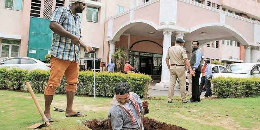 Workers dig a pit outside D Block at Secretariat, where CM K Chandrasekhar Rao will perform Bhumi Puja on Thursday