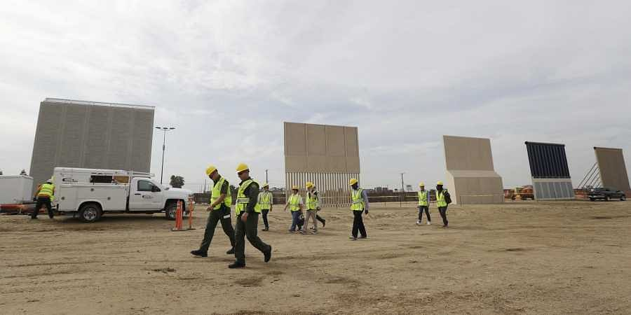 People pass border wall prototypes as they stand near the border with Tijuana, Mexico, in San Diego.