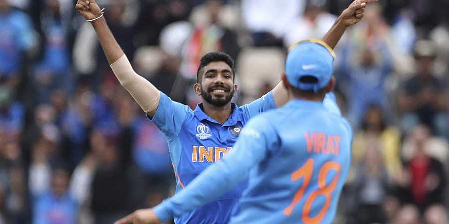 India's Jasprit Bumrah, left, celebrates with captain Virat Kohli. (Photo | AP)