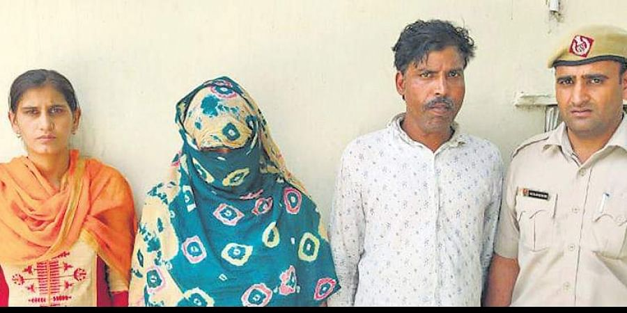 Accused Roshni (face covered in dupatta) and Naresh are produced before the media by the Faridabad police.