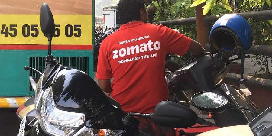 A delivery man working with the food delivery app Zomato sits on his bike in a business district in Mumbai