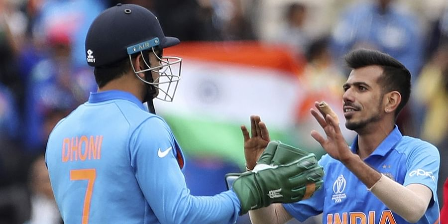 Yuzvendra Chahal, right, celebrates with teammate MS Dhoni the dismissal of South Africa's Andile Phehlukwayo. (Photo | AP)
