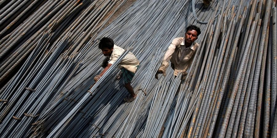Labourers load steel rods onto a truck at a steel factory on the outskirts of Jammu July 12, 2012. (File | Reuters)