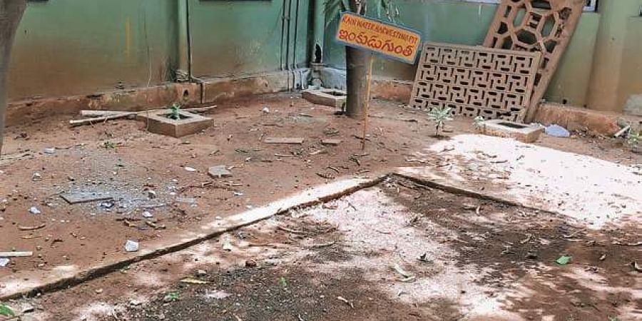A rainwater harvesting pit covered with mud at VMC office.