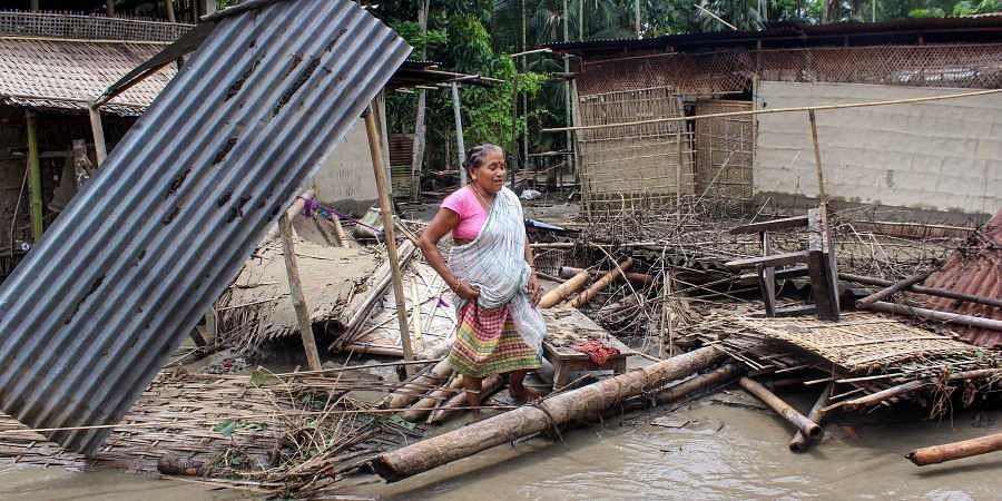 A woman stands near her damaged hut caused due to flooded area due to incessant rainfalls at Hajo in Kamrup on 13 July 2019. (Photo | PTI)
