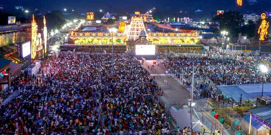 Devotees gather to witness the Garuda Seva at Tirumala temple.