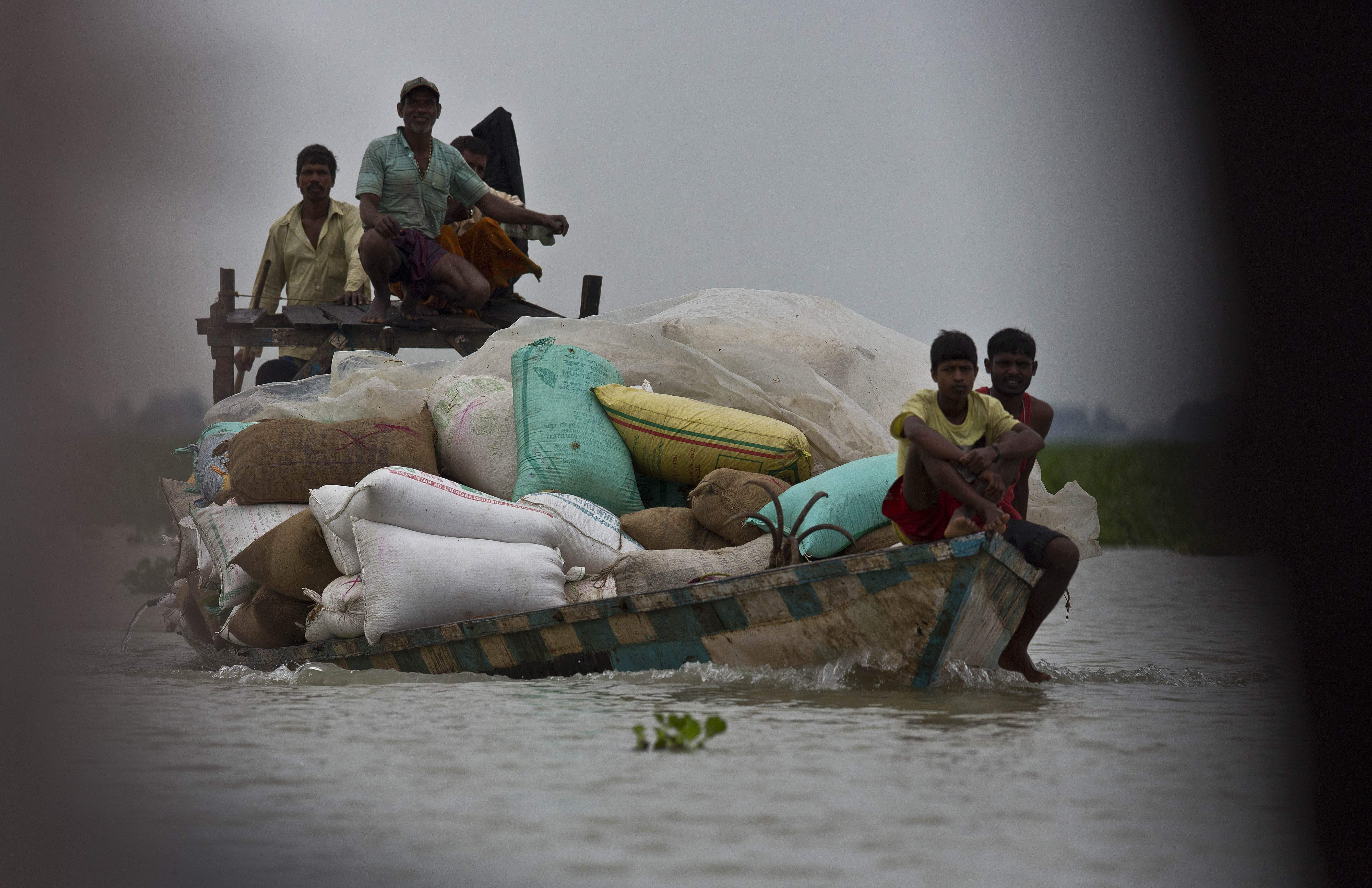 Villagers transport flood relief materials on a boat in Burgaon village, east of Gauhati, Assam.