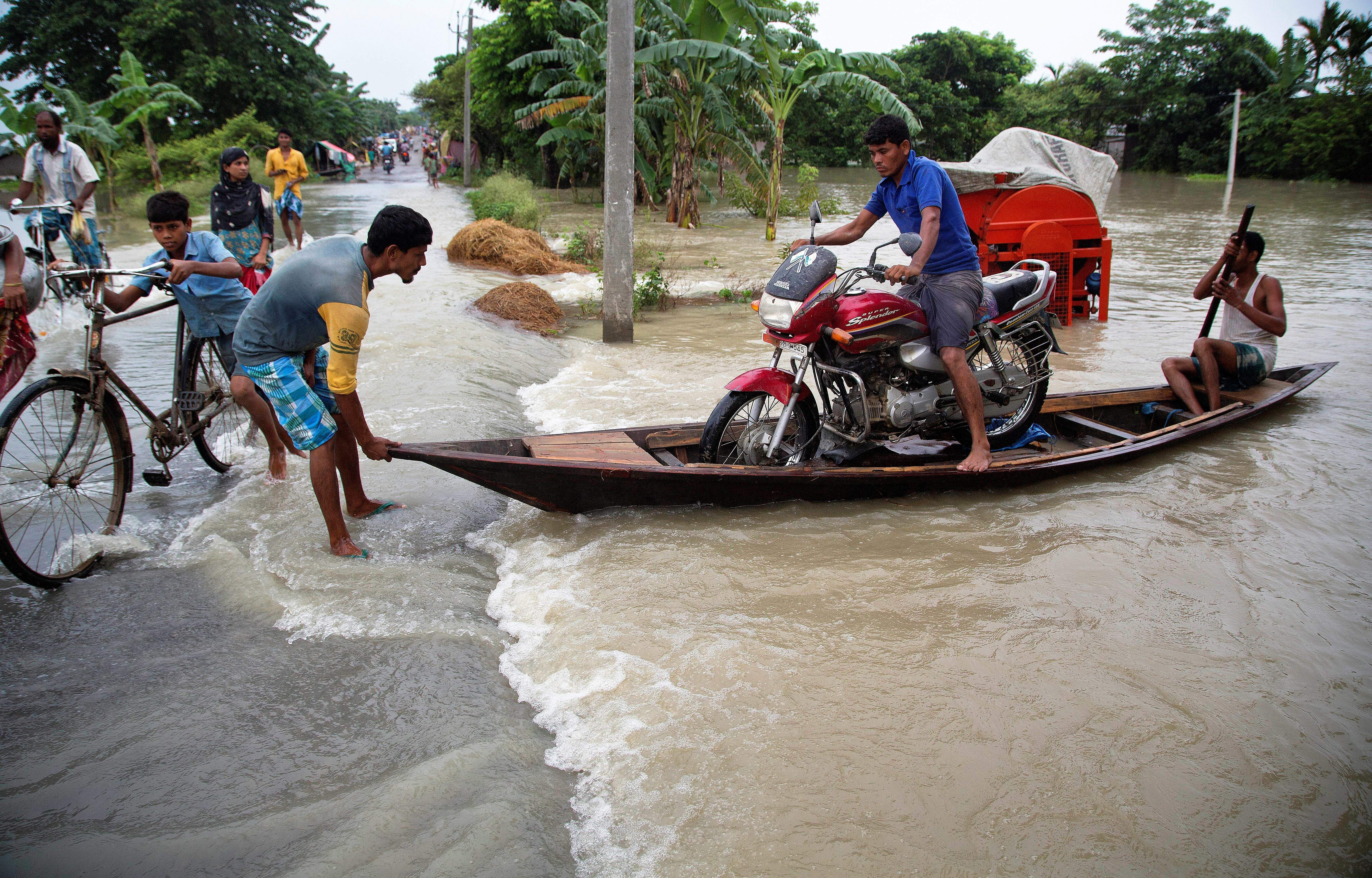 Flood affected villagers transport a motorcycle on a boat in Burha Burhi village, east of Gauhati, Assam.