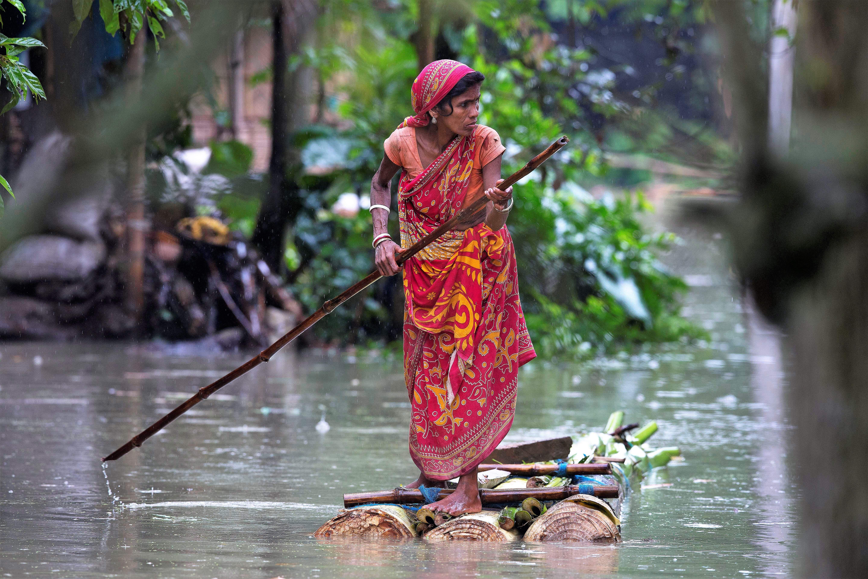 A woman rows a makeshift banana raft through flood waters in Burgaon, east of Gauhati, Assam.