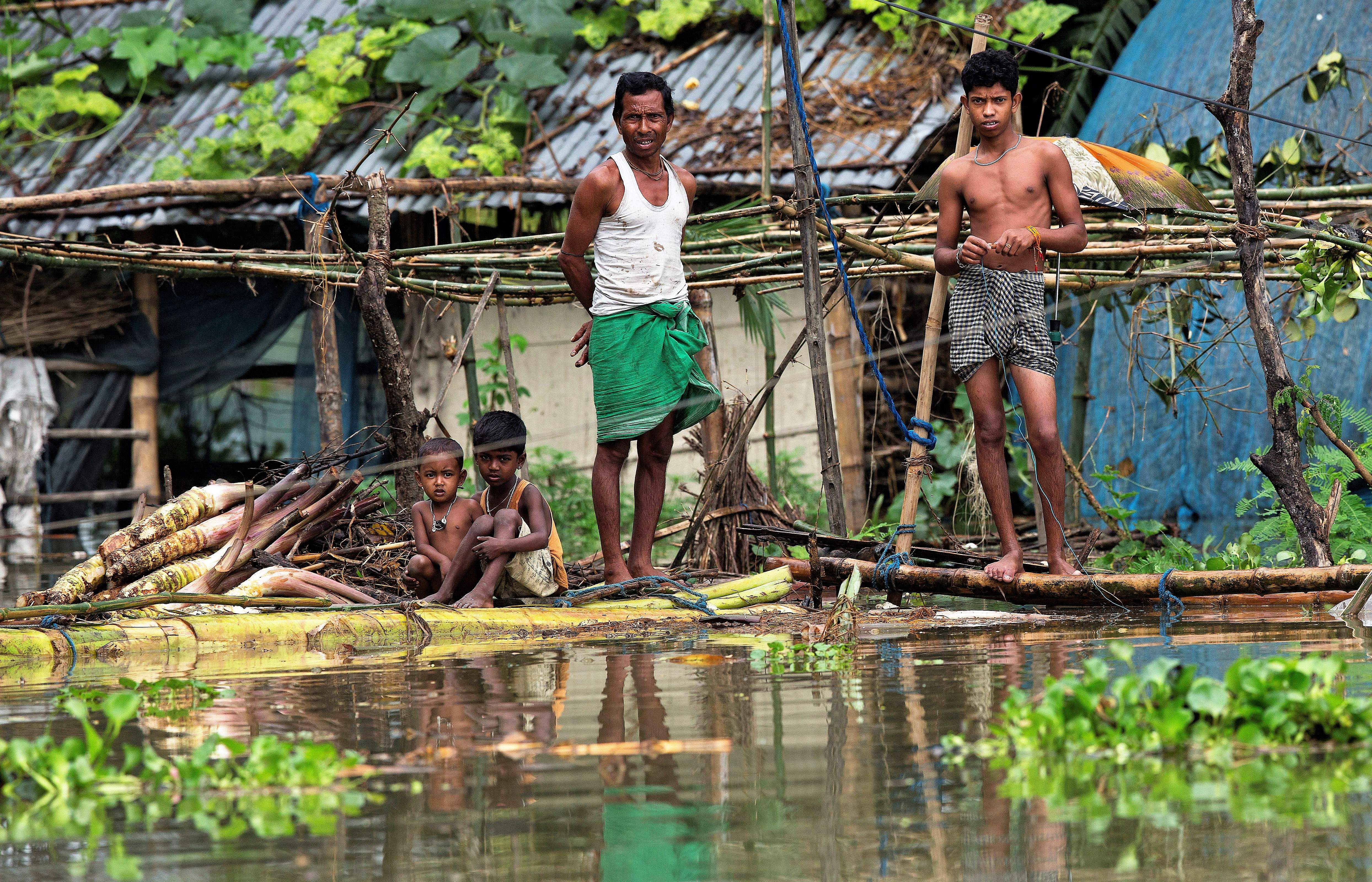 A flood affected family stands on a banana raft near their submerged house in Burgaon, east of Gauhati, Assam.