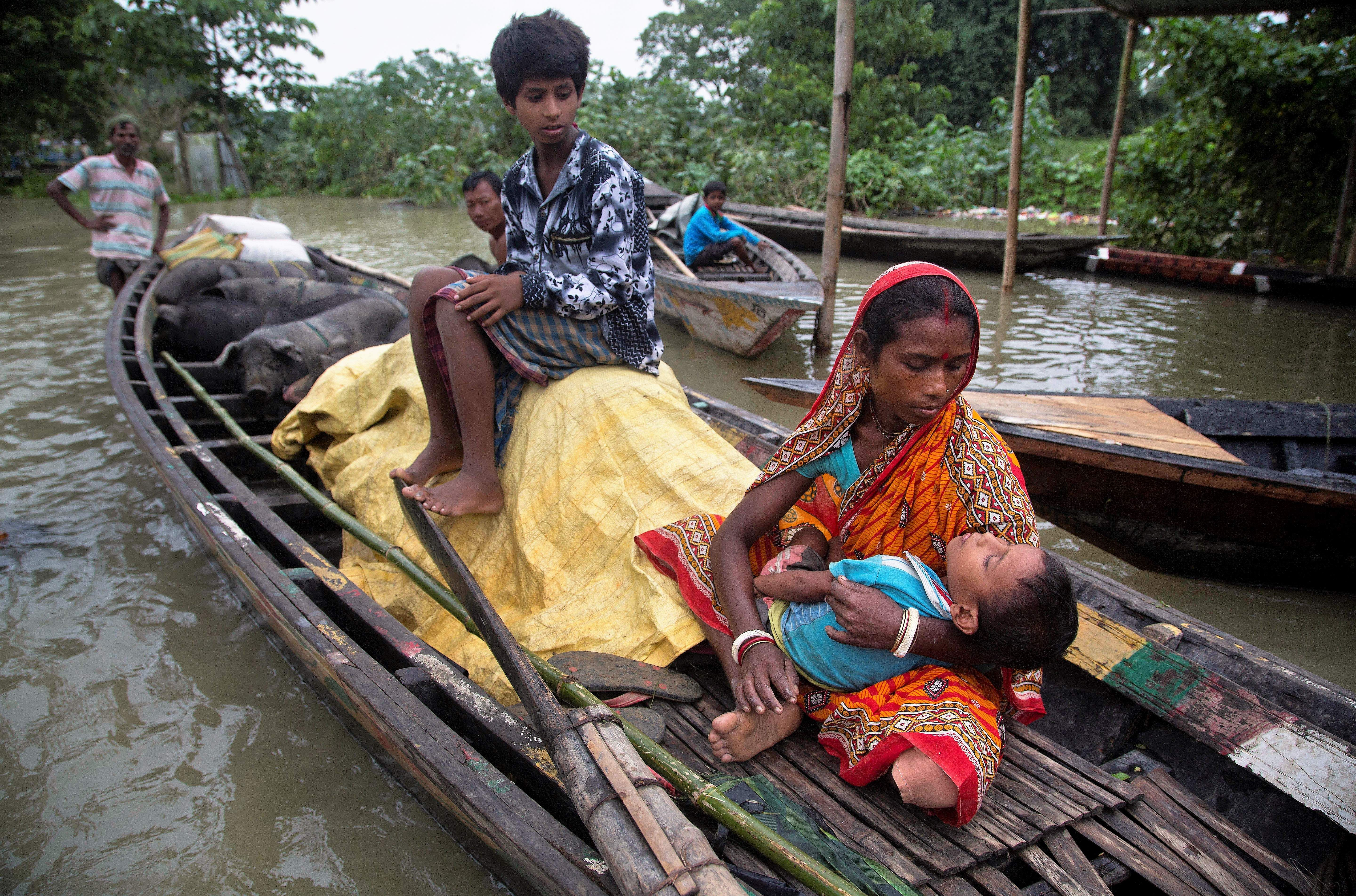 A flood affected woman carries her sick son on a boat in Burha Burhi village, east of Gauhati, Assam.